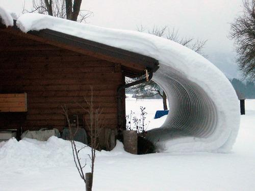 屋根からカールして垂れ下がっている雪