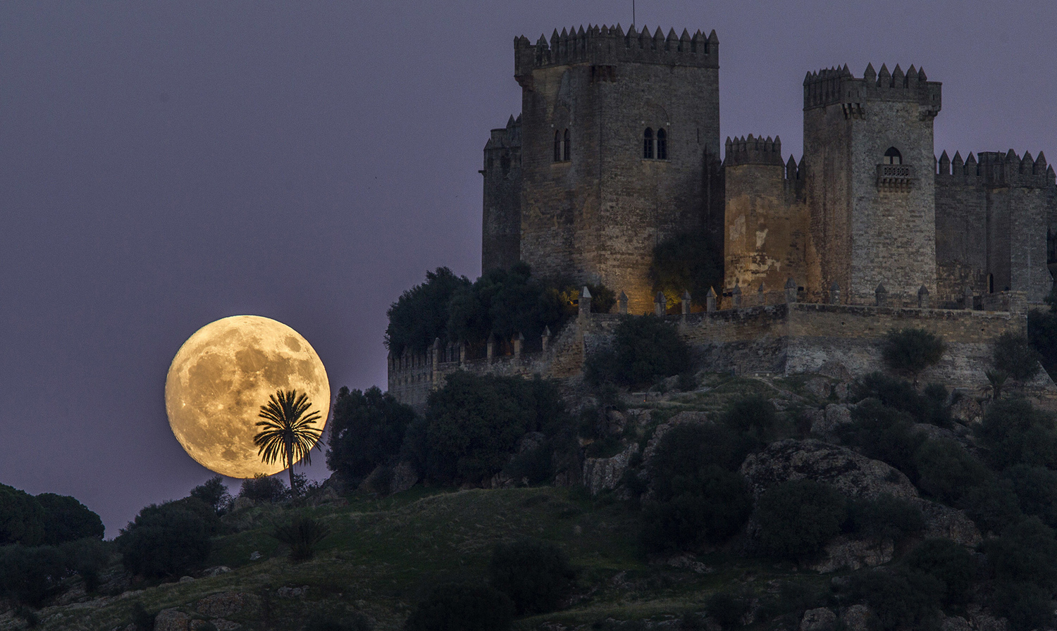 The moon rises behind the castle of Almodovar in Cordoba