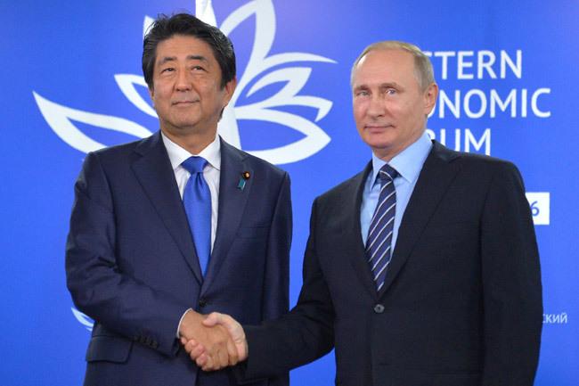 会談に臨み、握手する安倍晋三首相(左)とロシアのプーチン大統領(ロシア・ウラジオストク)=2016年9月2日【AFP=時事】