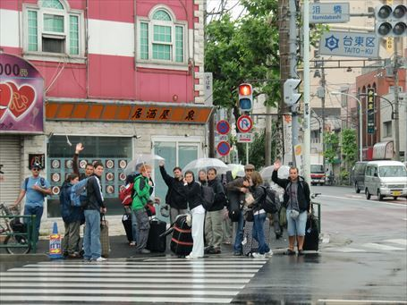 泪橋交差点で手を振る外国人旅行者