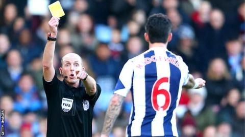 Referee Mike Dean cautions Liam Ridgewell
