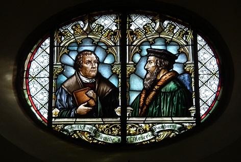 カルヴァン(右)が描かれたステンドグラス。左側はマルティン・ルター