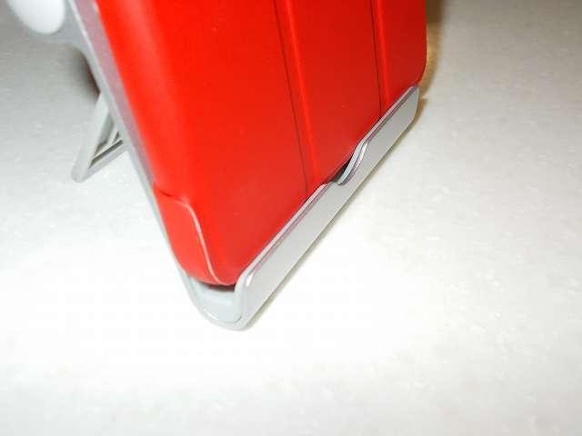 Amazon Fire タブレット 8GB 第5世代 2015 を装着した Fire 7 2015 ケース ATiC Amazon Fire 7 2015(第五世代) タブレット専用開閉式三つ折薄型スタンドケース レッド を、Anker Multi-Angle Stand タブレット用スタンド 77ANSTAND-SA Silver 溝部分にセットしたところ。厚みがあるため奥までセットできないが何とか倒れない程度に支えられている状態