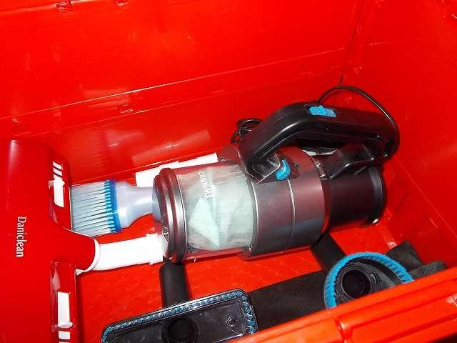 トラスコ中山 TRUSCO TR-C50B 薄型折りたたみコンテナ 50L ロックフタ付 レッドに、アイワ ふとん専用ダニクリーン ウェーブローラーを装着したままツインバード TWINBIRD ハンディークリーナー ハンディージェットサイクロン EX HC-EB51GY を収納したところ