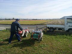 【写真】JA機械センターの方が草刈り機と動力噴霧器を軽トラに運んでいる様子